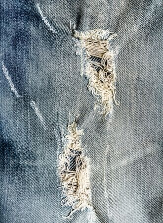 trendy hole on Denim Jeans. trendy frayed jeans, Ripped Destroyed Torn Blue jeans background. Close up