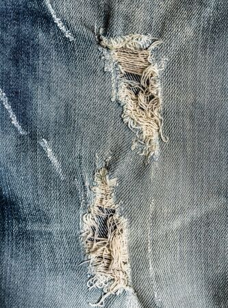 fashionable hole on Denim Jeans. Ripped Destroyed Torn Blue jeans background. Close up