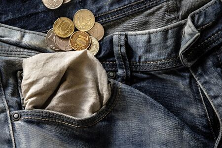 coins in blue jeans pocket turned inside out close-up, finance and currency concept