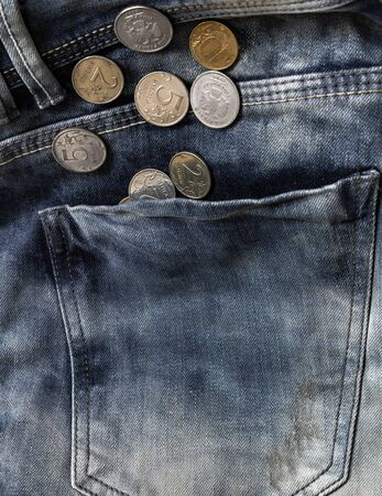 coins in blue jeans pocket close-up, finance and currency, saving and budget allocation