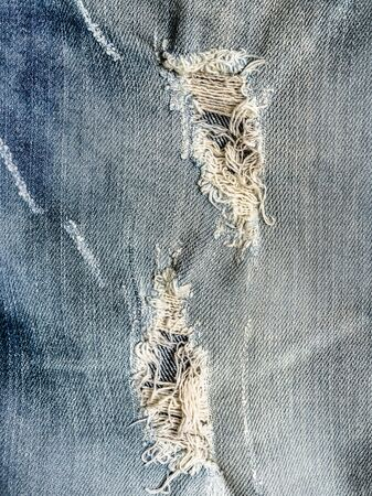 trendy hole on Denim Jeans. Ripped Destroyed Torn Blue faded jeans background. Close up Stock fotó