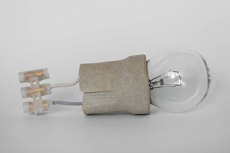 incandescent lamp bulb with cap, socket, wires and terminal block lies on white background. Bulb Ilyich and Edison, new idea concept