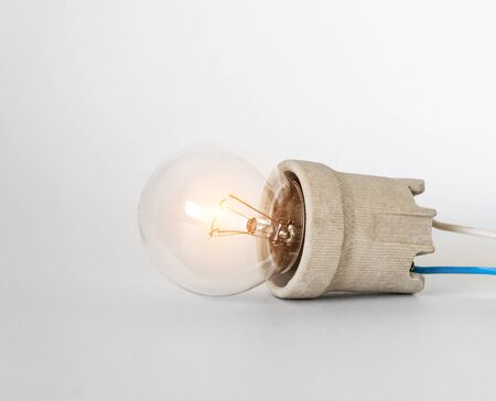Lighting incandescent lamp bulb with cap, socket, wires lies on white background. Bulb Ilyich and Edison, new idea concept with copy space