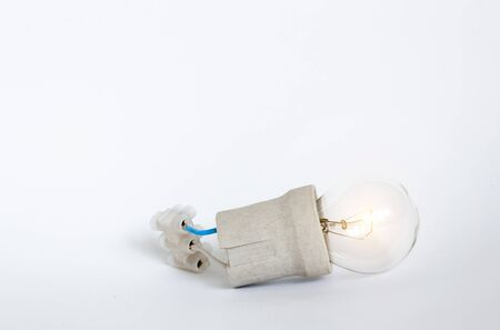 Lighting incandescent lamp bulb with cap, socket, wires and terminal block lies on white background. Bulb Ilyich and Edison, new idea concept, electrical work, safety