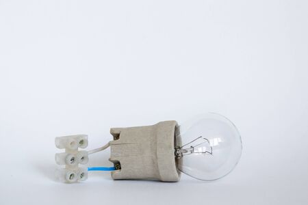 incandescent lamp bulb with cap, socket, wires and terminal block lies on white background. Bulb Ilyich and Edison, new idea concept Stock Photo