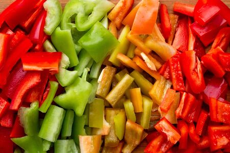colorful chopped bell peppers - red, yellow, green - cut in cubes, autumn cooking lecho, cooking peperonates, flat lay Archivio Fotografico