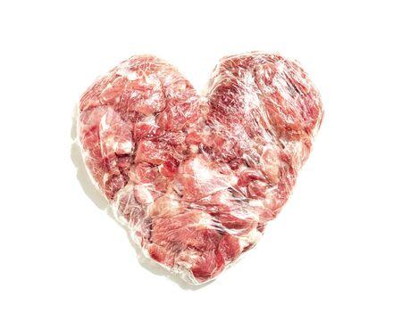 Nahaufnahme Frisches rotes Fleisch in Herzform auf weißem Hintergrund, in Folie verpacktes Essen, Schnitzel für Schnitzel