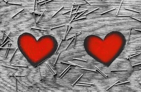two red paper hearts circled in black with empty space between them on wooden gray background surrounded by iron nails, couple relationship concept 免版税图像