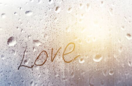 inscription love on a wet window pane with raindrops in the rain with sunlight outside