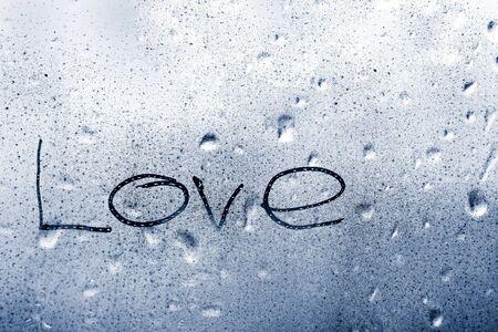 inscription love on a wet window pane with raindrops in the rain 免版税图像