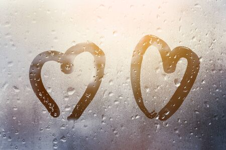 two hearts painted on glass in Rainy weather there are many drops on it and the sun shines outside the window at dusk between them, Valentine's Day concept