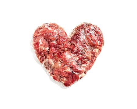 Fresh red meat in shape of heart on white background , film wrapped food, cutlet for cutlets