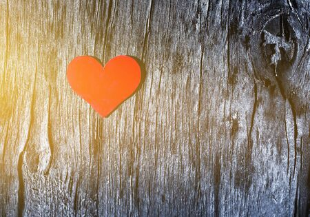 red heart on a old gray wooden cracked surface background with sun exposure, Valentine's day concept
