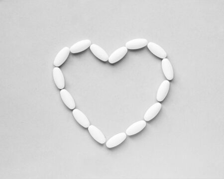 Heart shape made from pills for therapy, concept of treatment and health care on gray background 免版税图像