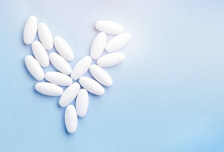 White pills in the shape of a heart on a blue background with sunlight. The concept of a healthy heart. Vitamins for the heart. Medical banner, copy space, place for text. 免版税图像