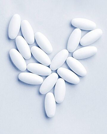 heart shaped medical white oval pills close-up isolated on classic blue background. Health treatment choice healthy lifestyle concept. Medical banner 免版税图像