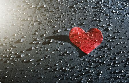 red heart in sunshine on raindrops background, Valentine's Day background, health and cardio concept