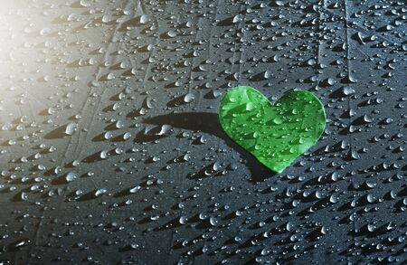 Green paper heart in drops of water on raindrops background, Valentine's Day background, health and cardio concept 免版税图像