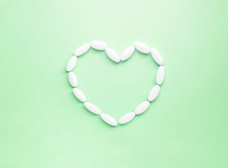 White heart shape made from pills for therapy, concept of treatment and health care on soft green background