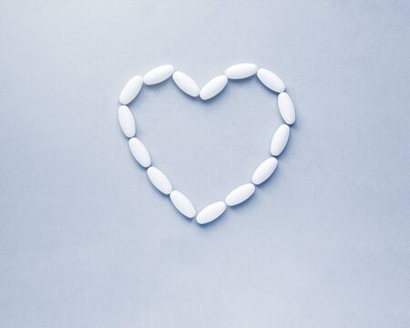 Heart shape made from pills for therapy, concept of treatment and health care on classic blue background