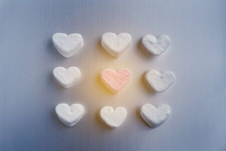 pink marshmallow heart lies among white sugar marshmallows square shaped, with sun flare on a gray aluminum background, valentines day concept 免版税图像
