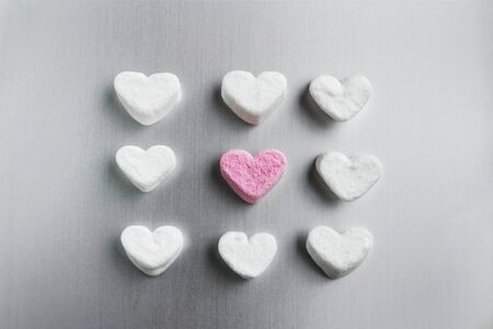 pink marshmallow heart lies among white sugar marshmallows square shaped on a gray aluminum background, valentines day concept