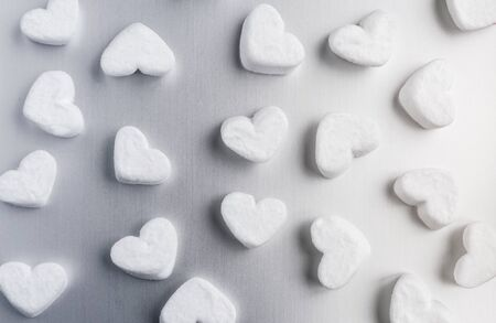 white sugar heart-shaped marshmallows evenly laid out on a gray aluminum background