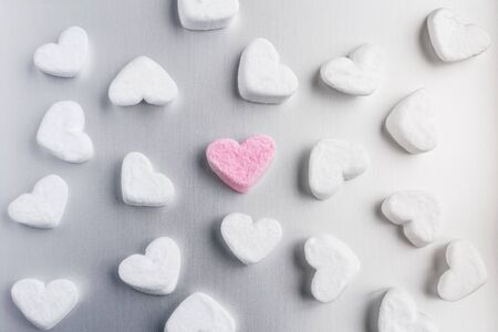 pink marshmallow heart lies among white sugar marshmallows in shape of hearts evenly laid out on a gray aluminum background