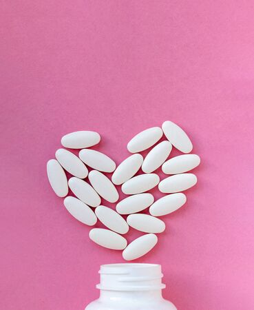Heart made of pills over the neck of a bottle on pink background. Copy space for text. Valentine's Day Pills 免版税图像