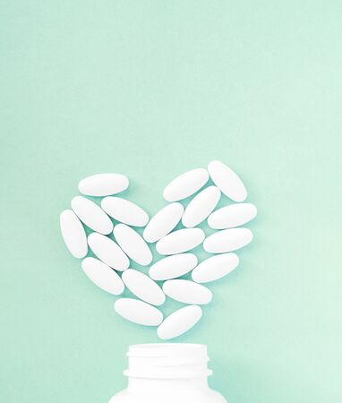 Heart made of pills over the neck of a bottle on on soft green background. Copy space for text. Valentine's Day Pills 免版税图像