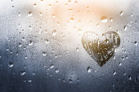 Heart painted on glass in Rainy weather, is fogged up and there are many drops on it