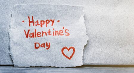 The inscription Happy Valentine's Day in red pencil on a piece of craft paper with a red heart. Copy space for text.