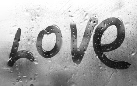inscription love with a finger on misted glass in rain with dripping raindrops