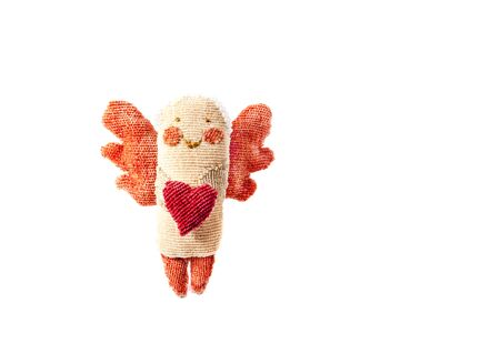 handmade figurine angel with wings holds in his hands a heart made of fabric isolated on a white background. Christmas Greeting card with copy space for inscription