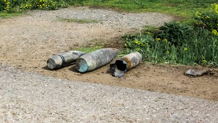 three artillery shells lie on the side of the asphalt road, in the summer dandelions bloom and the grass turns green. War concept, rusty shells 免版税图像