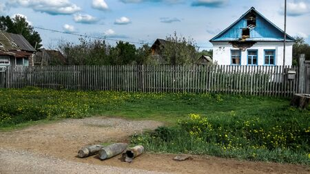 artillery shells lie on the side of the asphalt road near the village house, in the summer dandelions bloom and the grass turns green. Glass is broken in the house and the roof is damaged. 免版税图像