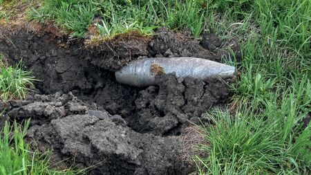 Unexploded new, brilliant artillery shell plowed and blew up the black earth on green grass. Peace and war