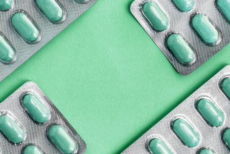 White blister pack of tablets pill statins for light resistance packaging on Aqua Menthe background. Aqua Menthe tablets, copy space in the center, tasty antidepressant