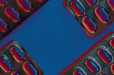Red and blue tablets in a blister pack thermal radiation, , pills in foil blister packs, medications drugs on blue surface. Medicines for various diseases. Top view. Copy space in the center 免版税图像