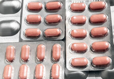 Several of aluminum blisters with colored pink tablets of different shapes close-up. Top view 免版税图像