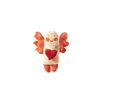 handmade figurine angel with wings holds in his hands heart made of fabric isolated on a white background. Greeting card for Easter with copy space for inscription