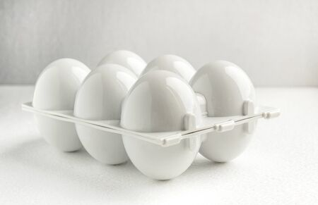 white plastic tray for six reusable eggs, close up. Environmental reusable concept, Happy Easter concept on white background