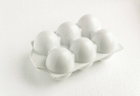 White plastic tray or container for six reusable eggs, top view close up. Environmental reusable concept, Happy Easter concept on white background. Minimalistic food concept