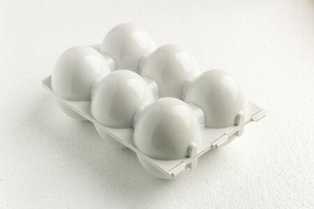 white plastic tray or container for six reusable eggs, close up. Environmental reusable concept, Happy Easter concept on white background