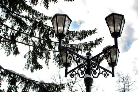 A cast-iron street lantern with snow caps at the top under the branches of spruce in winter, the concept of the New Year holidays and winter 免版税图像