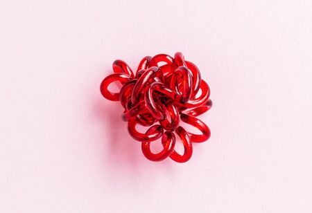Red spiral elastic hair ties twisted. Elastic hair tie on pink background close-up