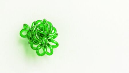 Green spiral rubber band twisted. Elastic hair tie on white background close-up, copy space for text