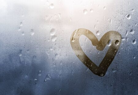 Heart painted on glass in Rainy weather, is fogged up and there are many drops on it, and the sun shines outside the window at dusk, toning in classic blue