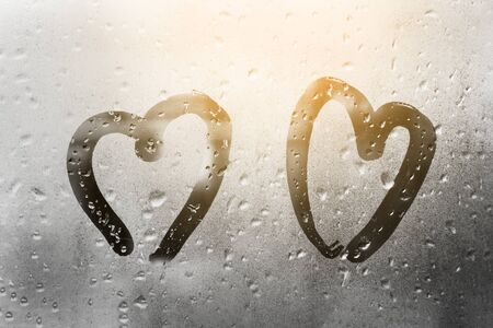two hearts painted on glass in Rainy weather there are many drops on it and the sun shines outside the window at dusk between them 免版税图像