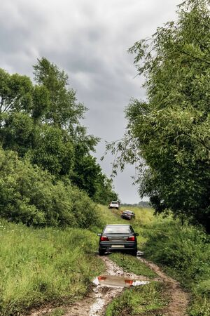 Passenger cars drive along a dirty forest road after rain against the backdrop of a summer landscape, the car got into a puddle